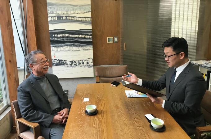 笑顔でインタビューに応じる藤江代表