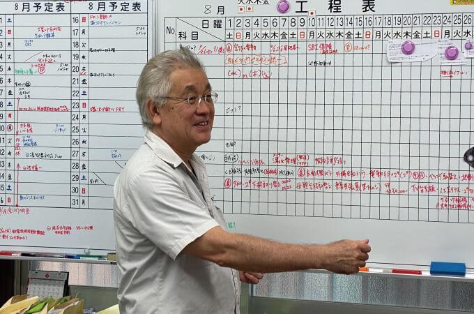 工程表のボードの前で説明する望月社長