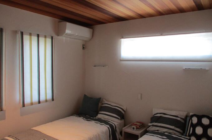 漆喰の壁と無垢材の天井でできた寝室