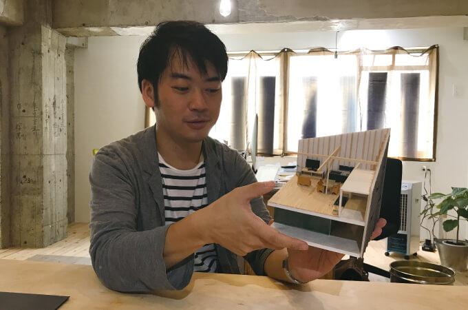 家の模型を手にする安田さん