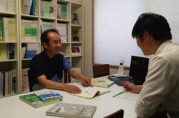 本を指さしながら説明する山田さん