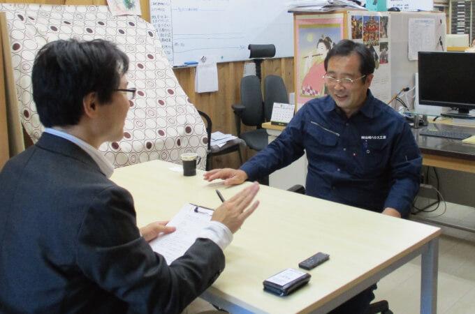 笑顔でインタビューに応じる山崎社長