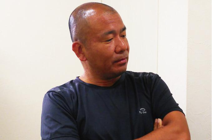 腕組みをする松本社長