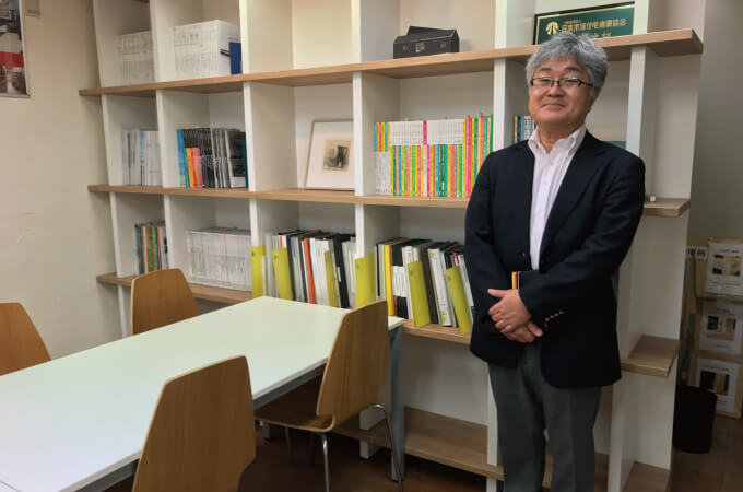 本棚の前に立つ中村さん