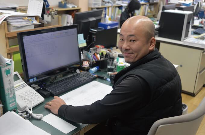 パソコンを操作しながら振り返る田中さん
